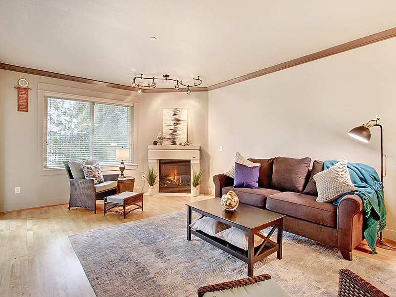 Lovely open living room with crown molding, gas fireplace and hardwood floors. A lovely view of the greenbelt.