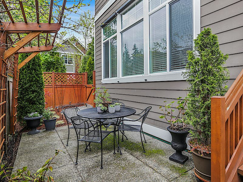 FULLY FENCED PRIVATE PATIO WITH ARBOR AND OUTDOOR SEATING