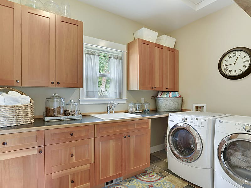 Conveniently located oversized main floor laundry room with plenty of counter space, storage and a utility sink.