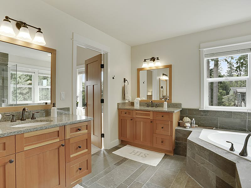 Spa-like master bath with fir cabinetry, heated slate floors, deep soaking tub and his/her vanities.