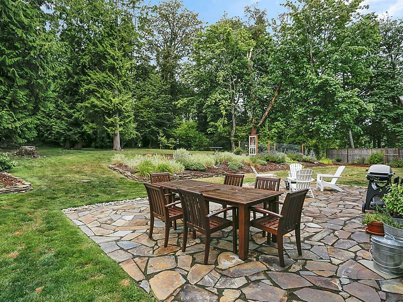 Private backyard with flagstone patio, raised vegetable beds in the distance and there is a new sport court with basketball hoop by garden beds that was installed after photo was taken.