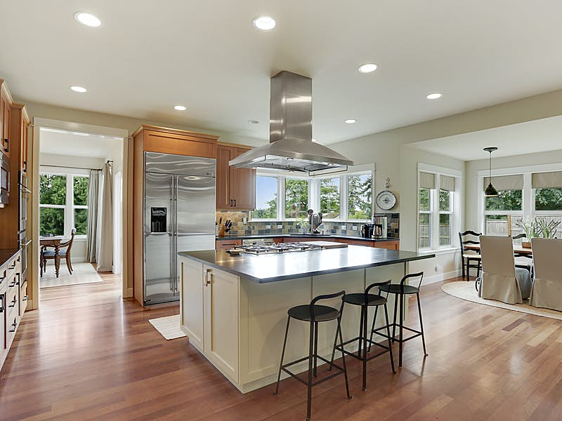 Gorgeous chef's kitchen with high end stainless appliances, gas range, double oven, large island with counter seating, slab quartz counters, and Fir cabinetry throughout. Informal dining area framed in a separate alcove.