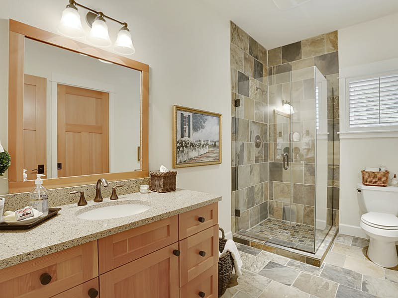 Main floor ensuite bathroom has a slate shower with glass surround and Fir cabinets.