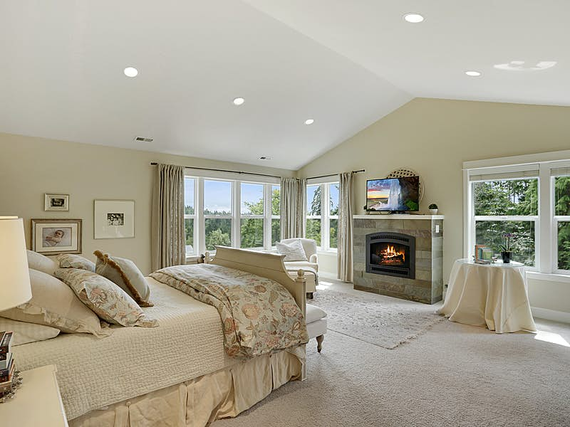 Luxurious master suite with vaulted ceilings, slate surround fireplace, lush carpeting and sweeping views.